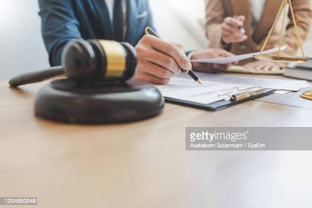 midsection of lawyer reading document on table - lawsuit stock pictures, royalty-free photos & images