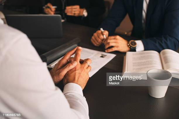 midsection of lawyer with client in meeting at law office - legal system stock pictures, royalty-free photos & images