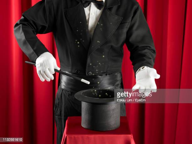 midsection of magician holding hat against red curtain - magic eye stock pictures, royalty-free photos & images