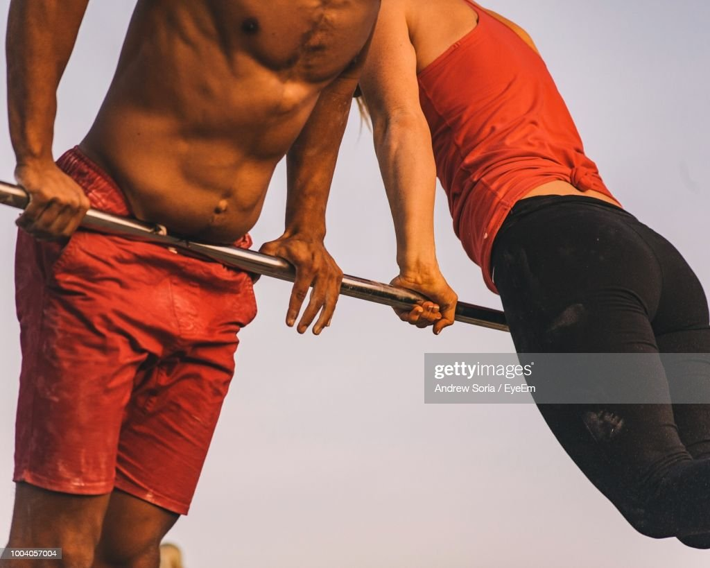Midsection Of Male And Female Athlete Exercising On Pole Against Clear Sky : Stock Photo