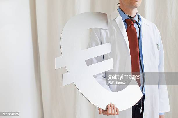 Midsection of male doctor holding euro symbol at clinic