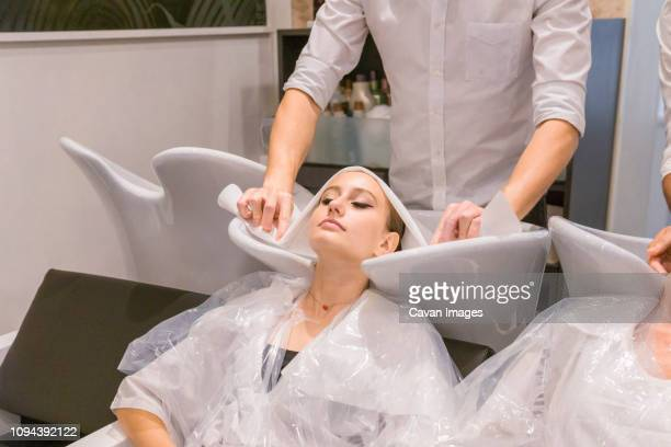 midsection of male hairdressers cleaning customers hair in salon - 頭をそらす ストックフォトと画像