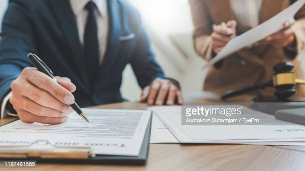 midsection of male lawyer working with coworker on table - justizwesen stock-fotos und bilder