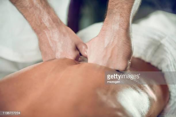 midsection of male massage therapist massaging shirtless female customer in spa - massaggio sensuale foto e immagini stock