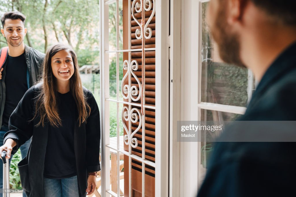 Midsection of male owner greeting guests at doorway of rental apartment : Foto stock