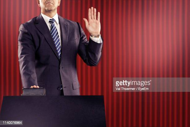 midsection of male politician taking oath at podium against red curtain - 宣誓 ストックフォトと画像
