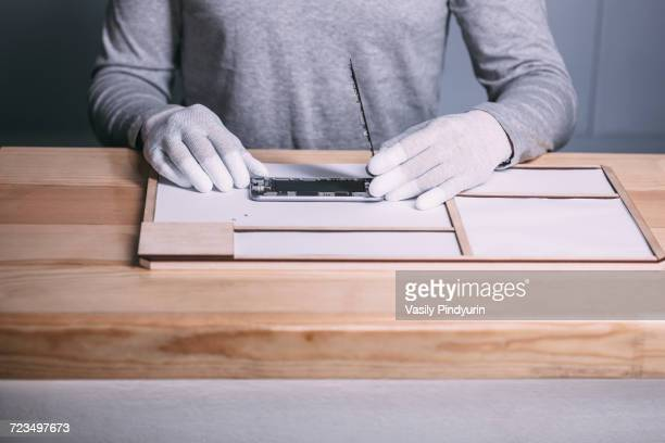 midsection of male technician opening smart phone at electronics store - white glove stock pictures, royalty-free photos & images