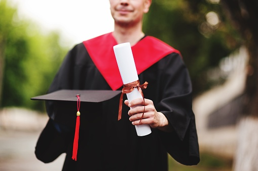 Midsection Of Male University Student Holding Degree - gettyimageskorea