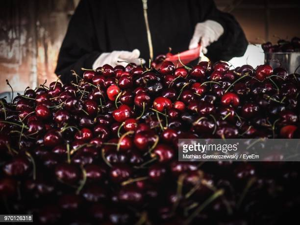 Midsection Of Male Vendor Selling Cherries At Market
