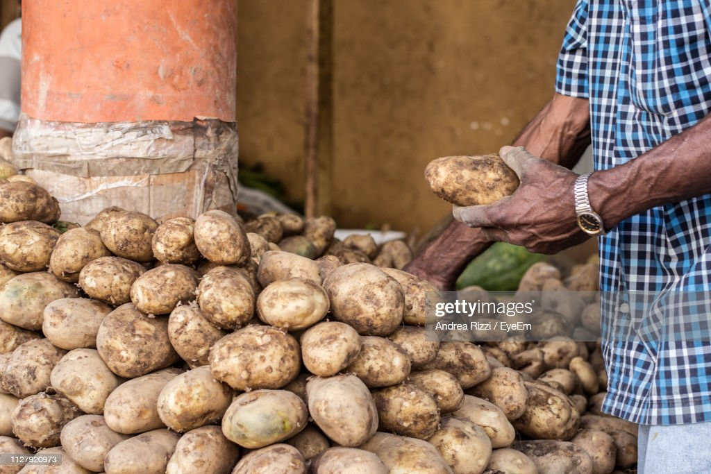 Midsection Of Male Vendor Selling Potatoes At Market : Foto stock