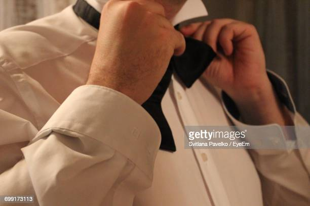 Midsection Of Man Adjusting Bow Tie