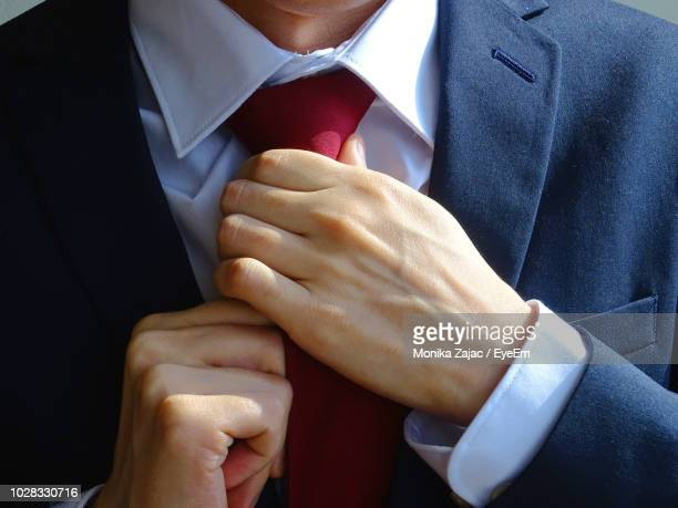midsection of man adjusting necktie - adjusting stock photos and pictures