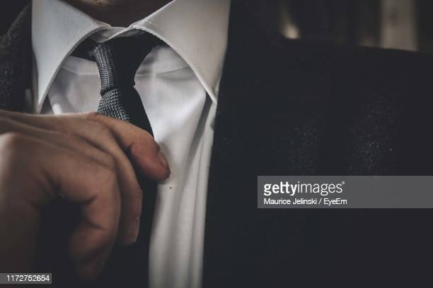midsection of man adjusting necktie - adjusting necktie stock pictures, royalty-free photos & images