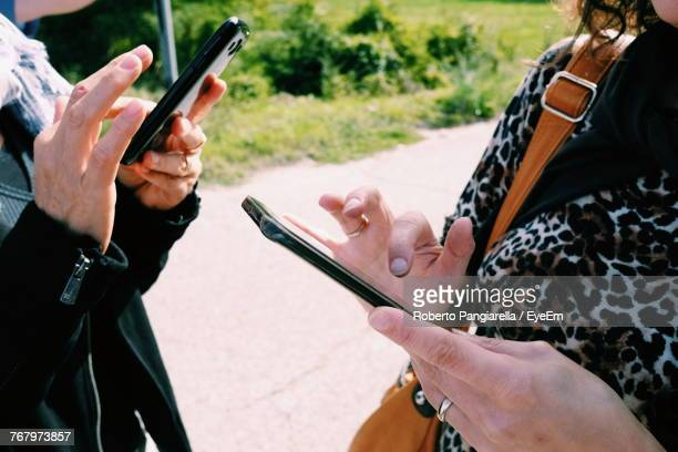 Midsection Of Man And Woman Using Smart Phone