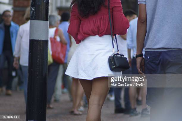 midsection of man and woman walking on street - women wearing short skirts stock pictures, royalty-free photos & images