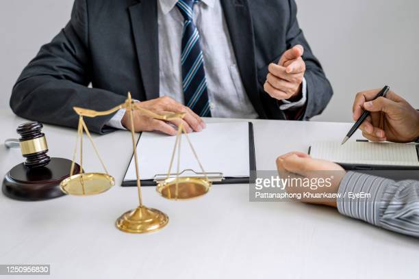 midsection of man and woman working on table - confession law stock pictures, royalty-free photos & images