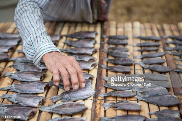 Midsection Of Man Arranging Fish On Table For Sale At Market Stall