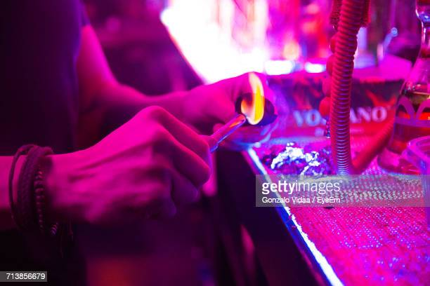 midsection of man burning coal by hookah in illuminated nightclub - chicha photos et images de collection