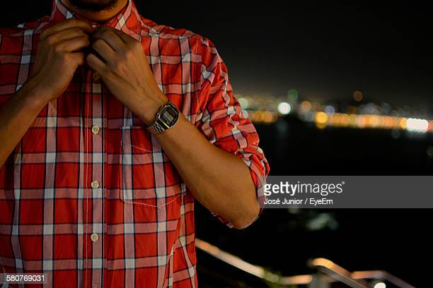 Midsection Of Man Buttoning Outdoors