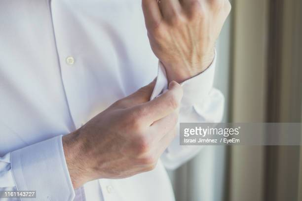 midsection of man buttoning shirt sleeve at home - all shirts stock pictures, royalty-free photos & images