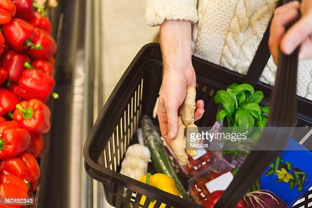 Midsection of man buying groceries at supermarket
