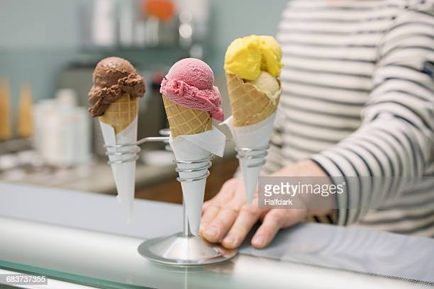 Midsection of man by various ice cream cones in stand at store