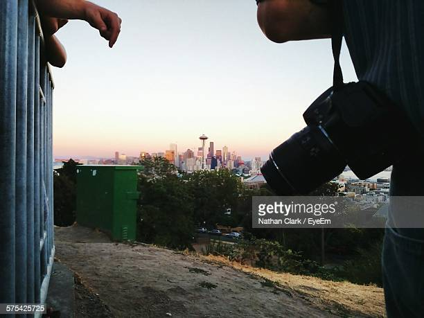 midsection of man carrying camera with cityscape in background - space needle stock-fotos und bilder