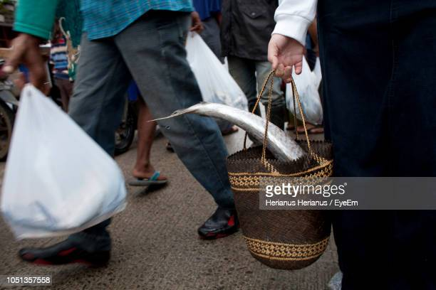 Midsection Of Man Carrying Fish In Bag At Market