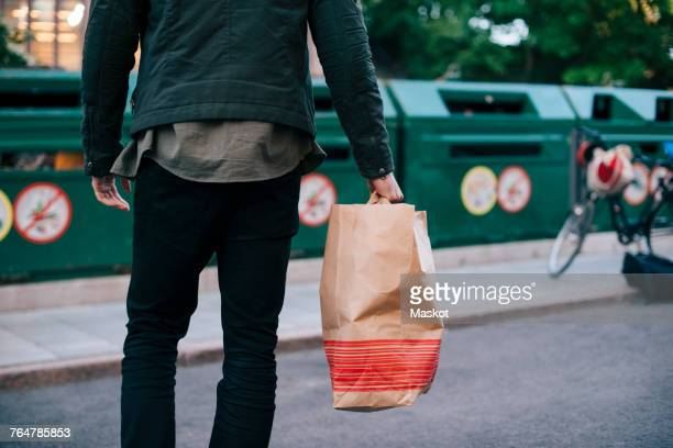 midsection of man carrying paper bag against garbage cans - reciclagem imagens e fotografias de stock