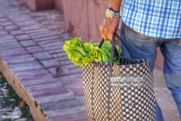 Midsection Of Man Carrying Vegetable In Bag