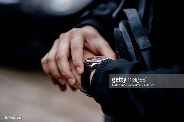 midsection of man checking the time - wrist stock pictures, royalty-free photos & images