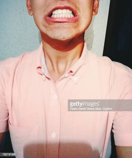 Midsection Of Man Clenching Teeth Against Wall