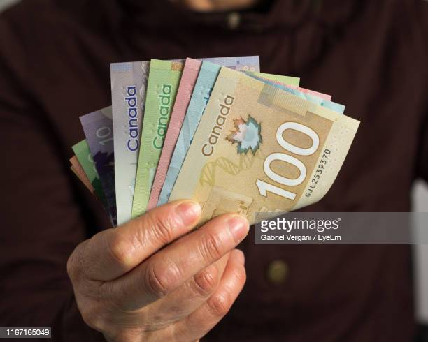 midsection of man counting money - canadian currency stock pictures, royalty-free photos & images