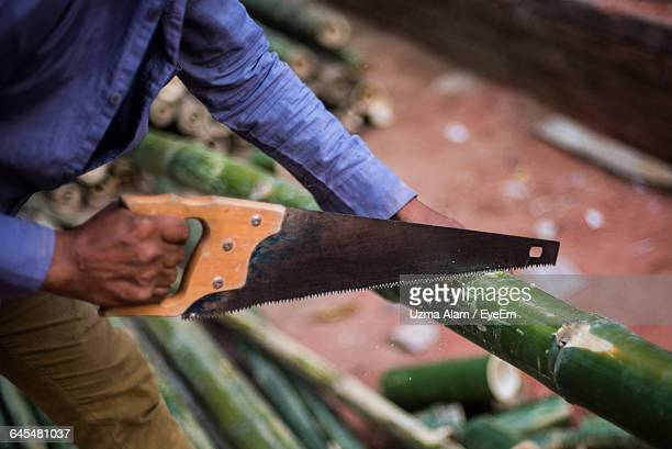 midsection of man cutting bamboo using hand saw - bamboo instrument stock photos and pictures