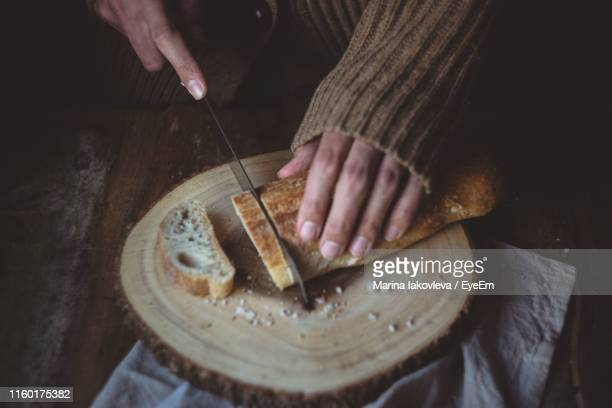 Midsection Of Man Cutting Bread On Table