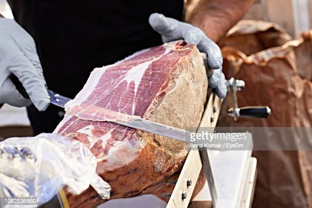 Midsection Of Man Cutting Raw Meat With Knife