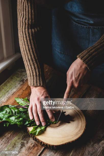 Midsection Of Man Cutting Vegetable On Table