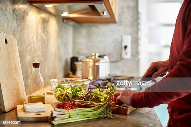 midsection of man cutting vegetables - gezonde voeding stockfoto's en -beelden