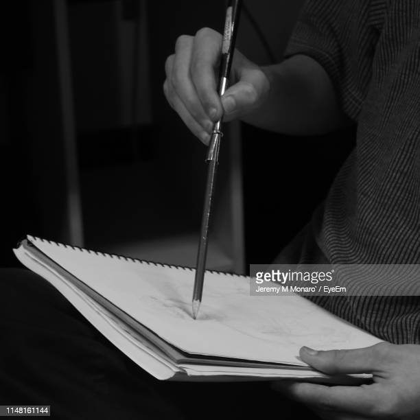 midsection of man drawing in book - jeremy monaro stock pictures, royalty-free photos & images