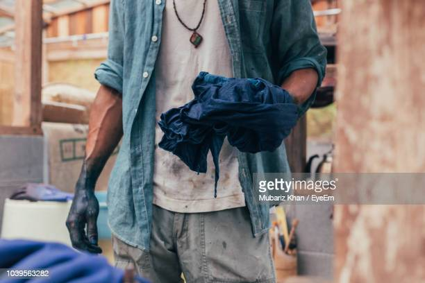 midsection of man dyeing clothe in factory - dye stock pictures, royalty-free photos & images