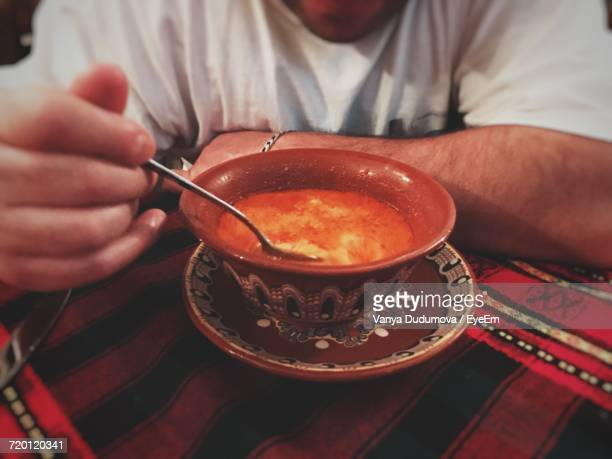 midsection of man eating fresh tripe soup in bowl on table - tripe photos et images de collection