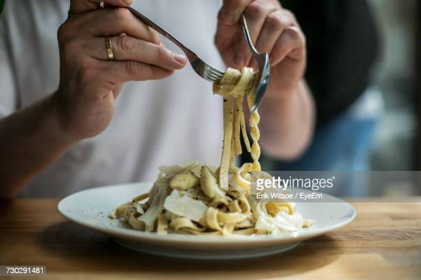 midsection of man eating pasta - pasta stock pictures, royalty-free photos & images