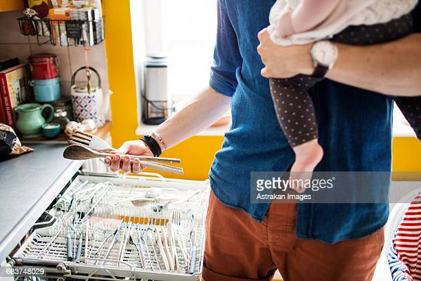 Midsection of man emptying dishwasher while carrying baby in kitchen
