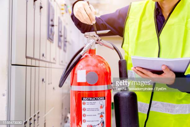Midsection Of Man Examining Fire Extinguisher