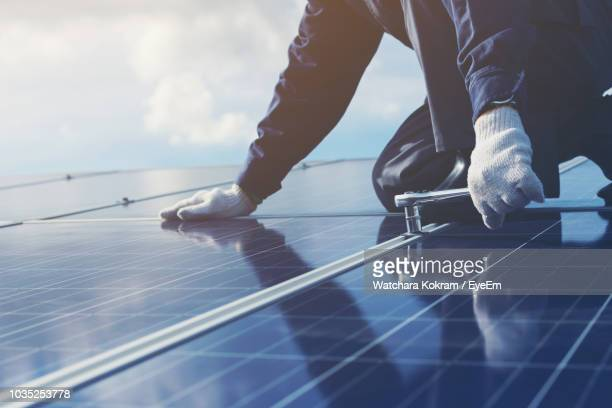 midsection of man examining solar panels against blue sky - solar energy stock pictures, royalty-free photos & images