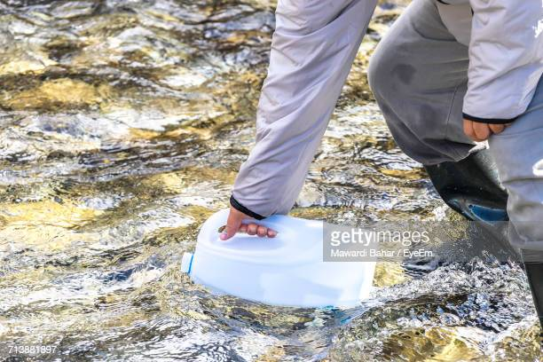 Midsection Of Man Filling Gallon From Flowing Water In Stream