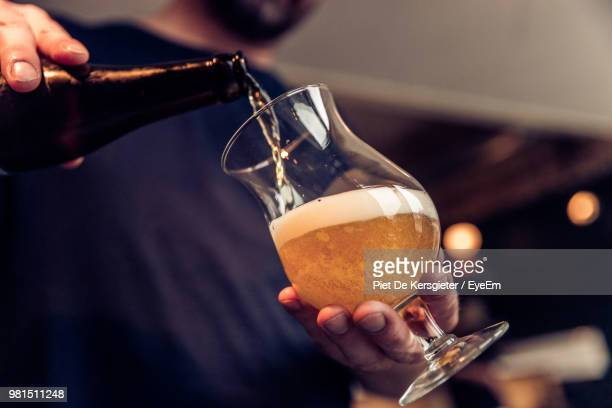 midsection of man filling wineglass with beer - transbordar imagens e fotografias de stock