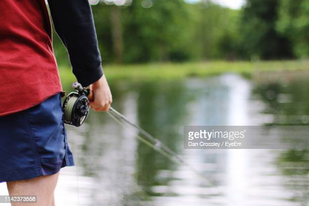 Midsection Of Man Fishing By Lake