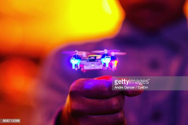 midsection of man gesturing by illuminated drone flying - drone foto e immagini stock