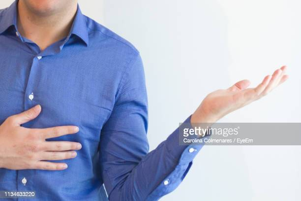midsection of man gesturing while standing against white background - gesturing stock pictures, royalty-free photos & images
